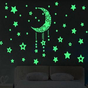 habitación con un sofa y en su fondo de pared un dibujo con pintura fosforescente de unas estrellas y una luna